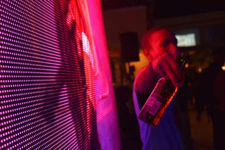Backlight Image of Adult male Holding up a beer bottle